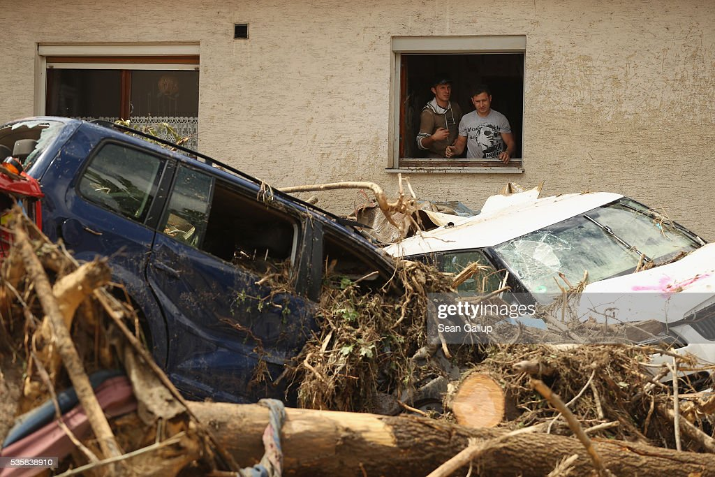 Two men throw ruined household items from the window of a house next to cars smashed among debris following a furious flash flood the night before on May 30, 2016 in Braunsbach, Germany. The flood tore through Braunsbach, crushing cars, ripping corners of houses and flooding homes during a storm that hit southwestern Germany. Miraculously no one in Braunsbach was killed, though three people died as a result of the storm in other parts of the country.