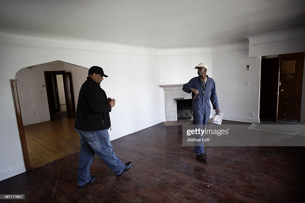 Two men tour one of twelve homes being auctioned off in the East English Village neighborhood April 27, 2014 in Detroit, Michigan. The city of Detroit and the Detroit Land Bank will auction off 12 homes starting May 5. One home will be auctioned off per day with an opening bid of $1,000.