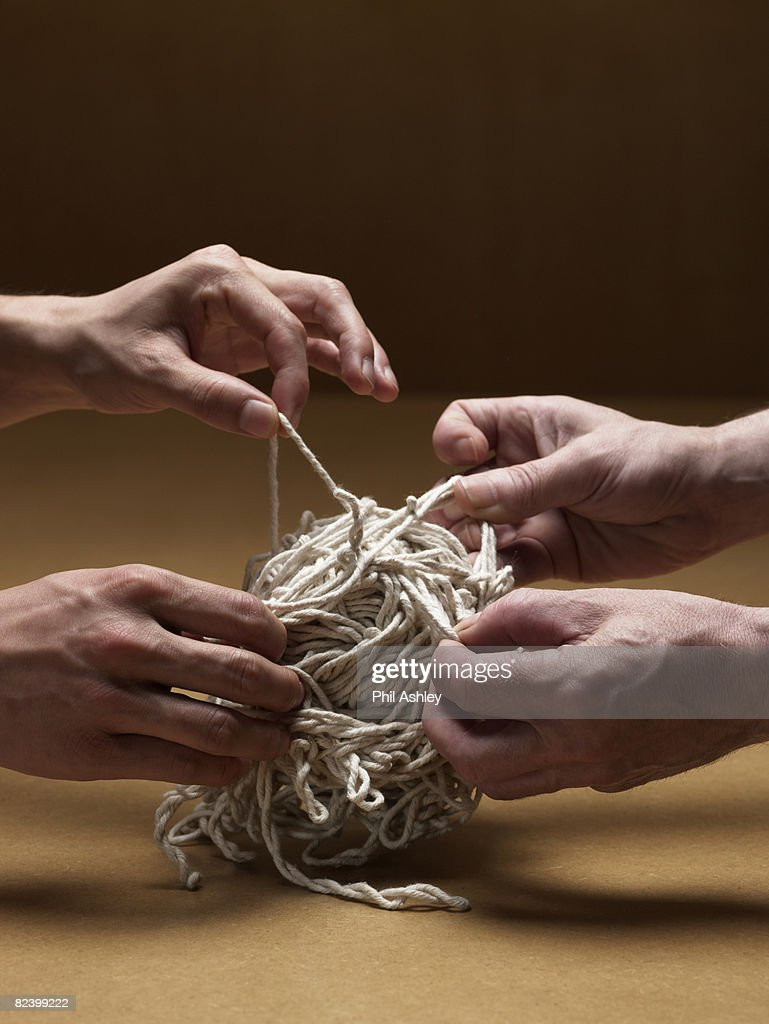 two men trying to untangle a giant knot