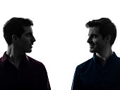 two caucasian young men twin brother friends looking at each others in shadow white background