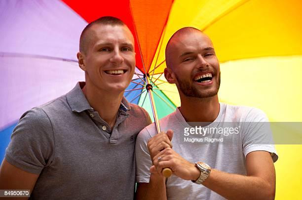 Two men under an rainbow umbrella Denmark.
