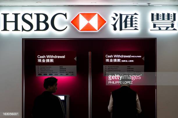 Two men use ATM machines at an HSBC branch in Hong Kong on March 4 2013 HSBC is expected to announce its annual profit in London on March 4 AFP PHOTO...
