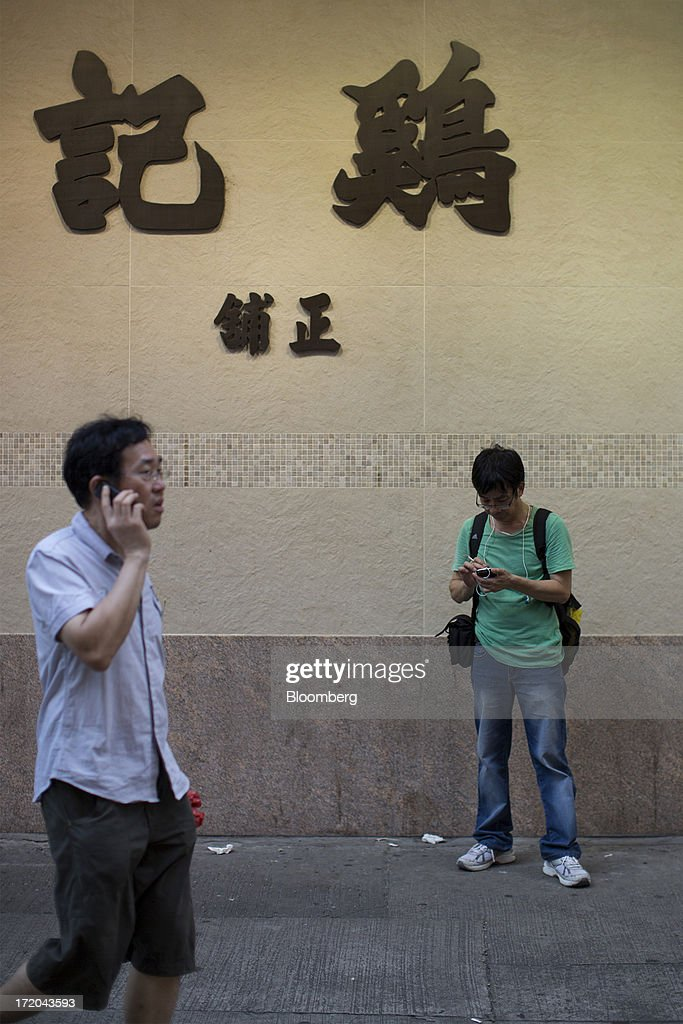 Two men use mobile phones in front of Kai Kee Mahjong School in the Yau Ma Tei district of Hong Kong, China, on Saturday, June 29, 2013. Hong Kongs best-selling newspapers called on readers to join a march to mark the anniversary of the citys handover to China, saying the government has failed to address issues of poverty and universal suffrage. Photographer: Jerome Favre/Bloomberg via Getty Images