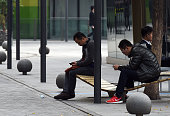 Two men use smartphones in a shopping area in Beijing on October 22 2014 Apple CEO Tim Cook met a senior Chinese official on October 22 days after...