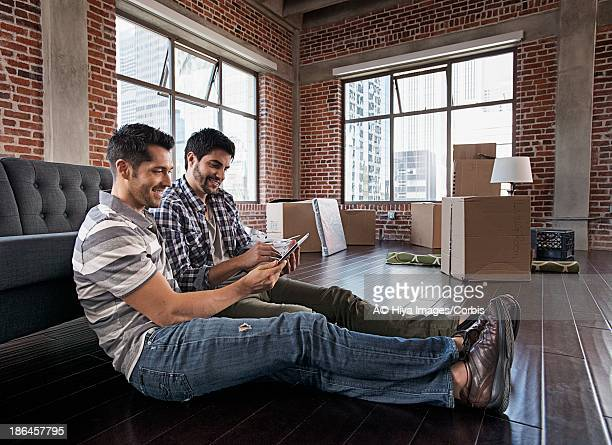 Two men using tablet PC in new apartment
