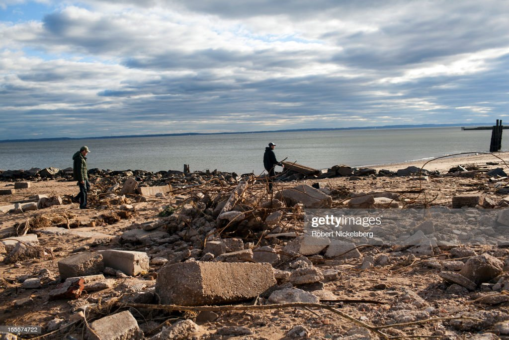 Two men walk along the shoreline after Superstorm Sandy November 3, 2012 in New Dorp Beach in the Staten Island borough of New York. The storm left millions without power or water and affect business and daily life.