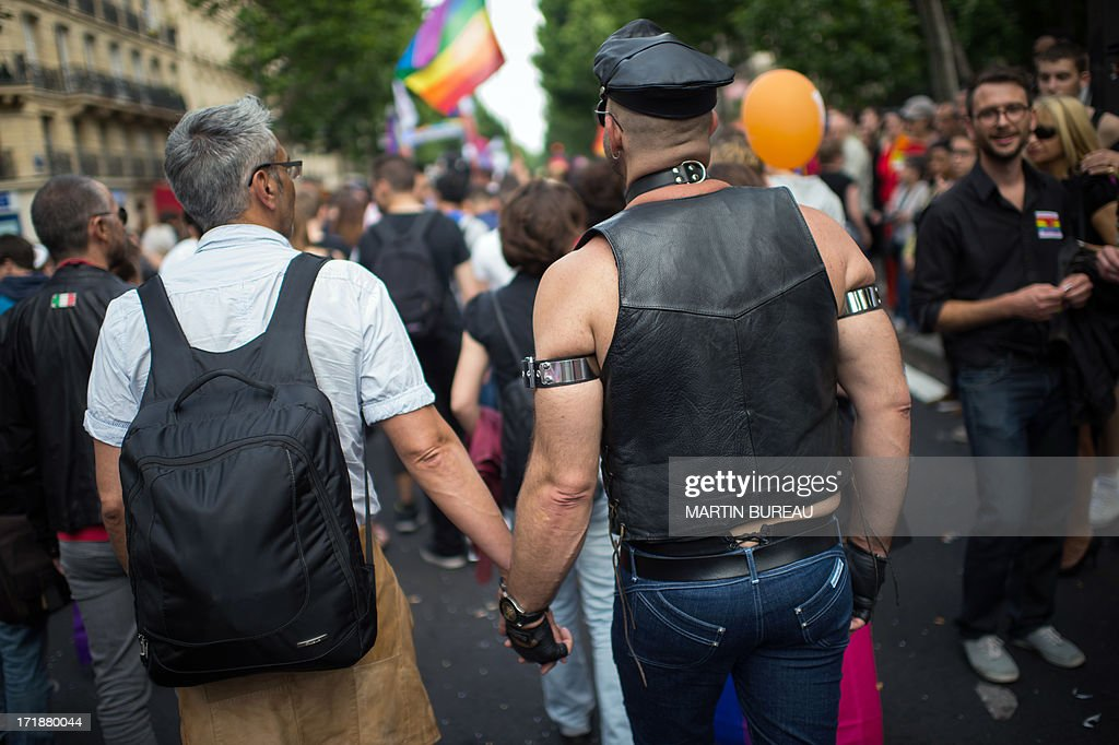 Two men walk hand in hand during the homosexual, lesbian, bisexual and transgender (HLBT) visibility march, the Gay Pride, on June 29, 2013 in Paris, exactly one month to the day since France celebrated its first gay marriage.