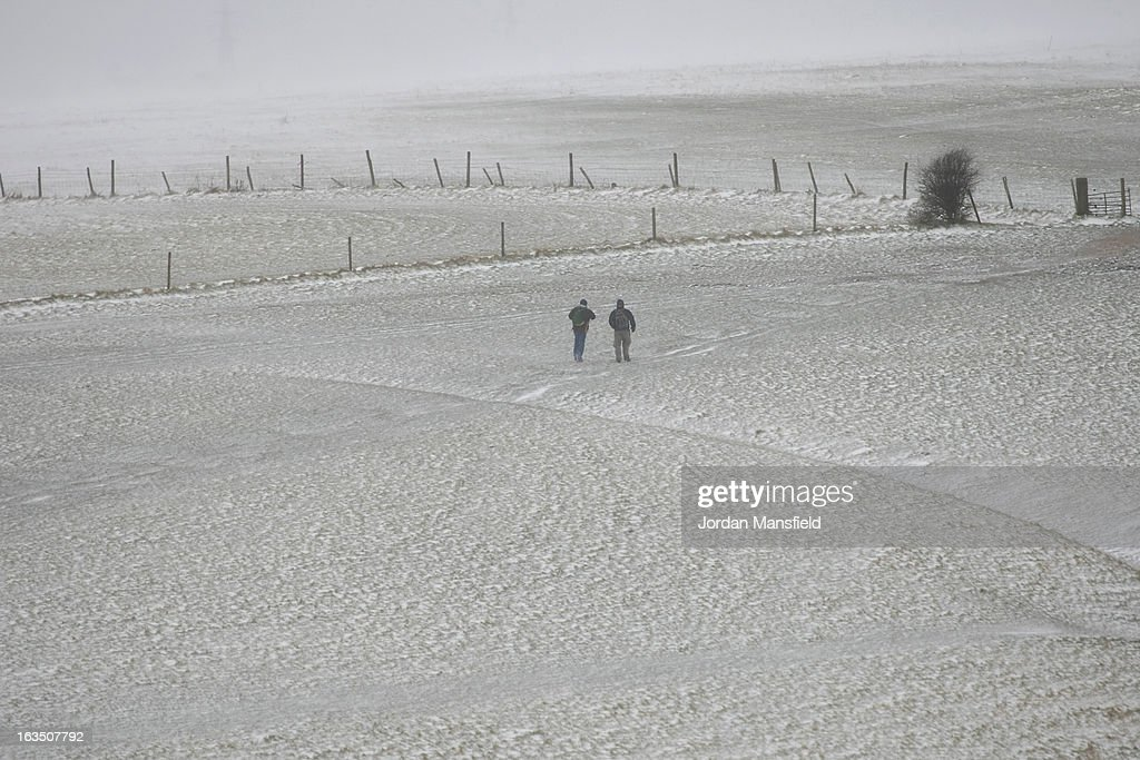 Two men walk in the snow at Devils Dyke on the South Downs on March 11, 2013 in Brighton, United Kingdom. Snowfall is affecting Southern parts of the UK with yellow severe weather warnings issued for London and South-East England.