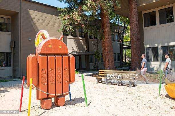 Two men walk near a sculpture representing Version 44 of the Android cellphone operating system which was nicknamed 'Kit Kat' at the Googleplex...