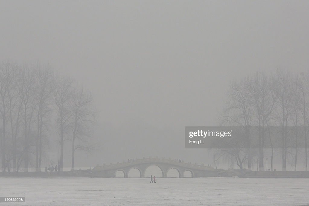 Two men walk on a frozen lake during severe pollution on January 30, 2013 in Beijing, China. The fourth round of heavy smog to hit Beijing in one month has sent more people to the hospital with respiratory illnesses and prompted calls for legislation to curb pollution. The haze choking many Chinese cities covers a total area of 1.3 million square kilometers, the China's Ministry of Environmental Protection said Tuesday.