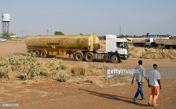 Two men walk on March 2 2014 near the Paloch oil fields in Upper Nile State the site of an oil complex and key crude oil processing facility in the...
