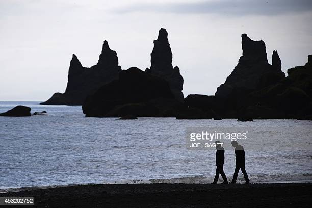 Two men walk on the black sand beach of Vik with a view on the basalt sea stacks called Reynisdrangar south Iceland on July 7 2014 AFP PHOTO / JOEL...