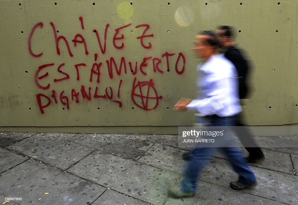 Two men walk past a graffiti reading 'Admit it, Chavez is Dead', in Caracas, on January 3, 2013. Top Venezuelan officials gathered in Cuba on Thursday amid growing demands for news about cancer-stricken President Hugo Chavez' condition, days before he is to be sworn in for another term. The Venezuelan president has not been seen since he underwent a long and complicated surgery for a recurrence of cancer 23 days ago, and officials have acknowledged that his recovery has been difficult.
