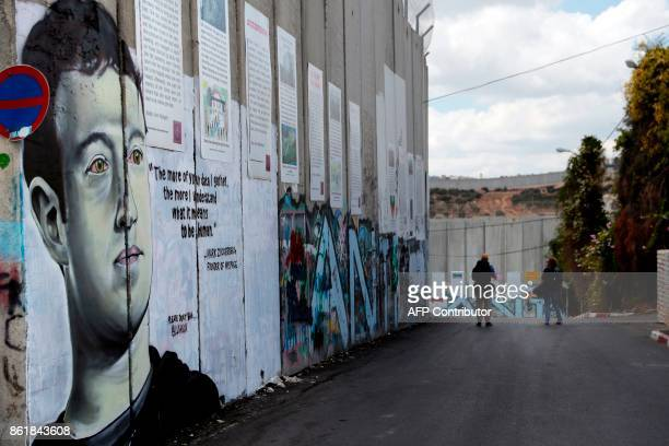 Two men walk past a new piece of graffiti depicting Chief Executive Officer and founder of Facebook Inc Mark Zuckerberg on the controversial Israeli...