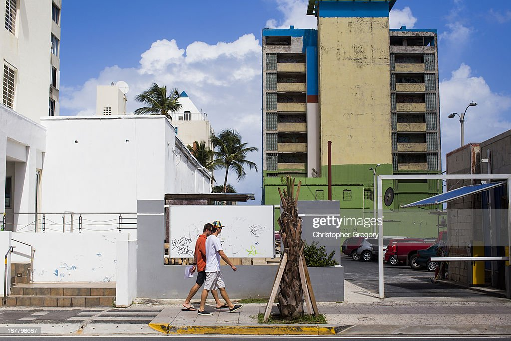 Two men walk past a vacant building on November 12, 2013 in the upscale Condado neighborhood of San Juan, Puerto Rico. The island territory of the United States, Puerto Rico, is on the brink of a debt crisis as lending has skyrocketed in the last decade as the government has been issuing municipal bonds. Market analysts have rated those bonds as junk and suspect it's 70 billion dollar debt might be unserviceable in the near future. With no industry other than tourism and the recent collapse of the real estate market, the way out is unclear.