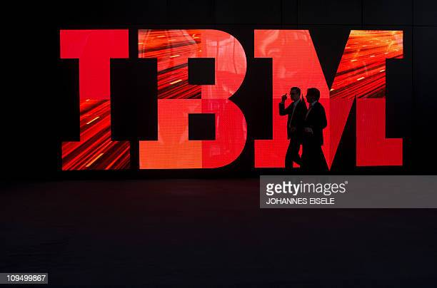 Two men walk past an IBM logo during preparations for the CeBIT IT fair on February 28 2011 in Hanover central Germany The world's top hightech fair...
