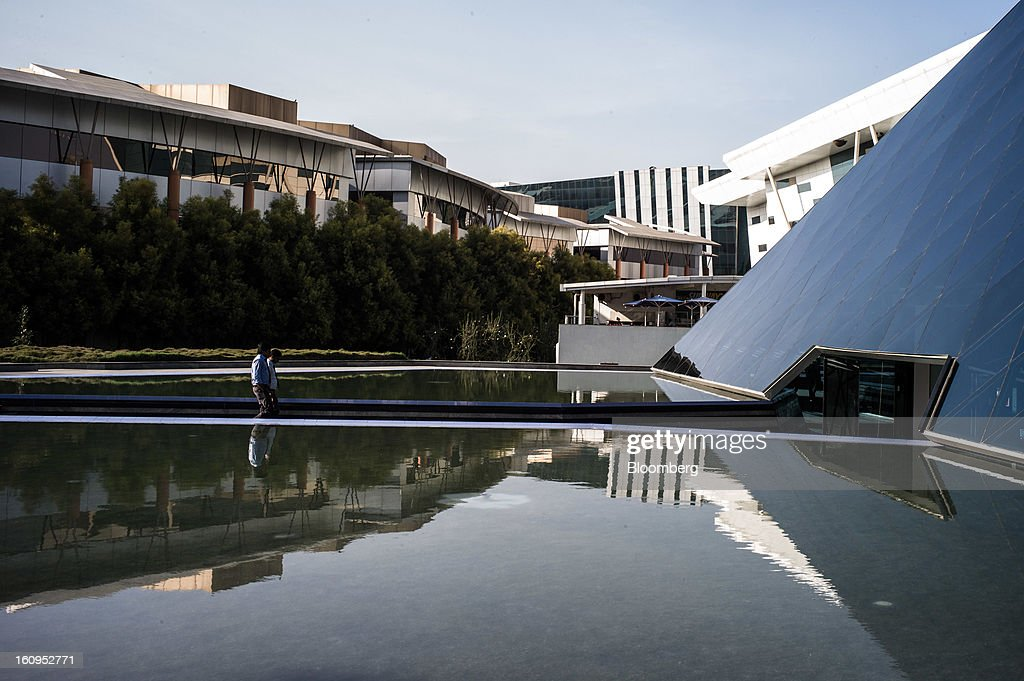 Two men walk towards the K. Dinesh Communication Design Center at the Infosys Ltd. campus in Electronics City in Bangalore, India, on Monday, Feb. 4, 2013. Infosys is India's No. 2 software exporter. Photographer: Sanjit Das/Bloomberg via Getty Images