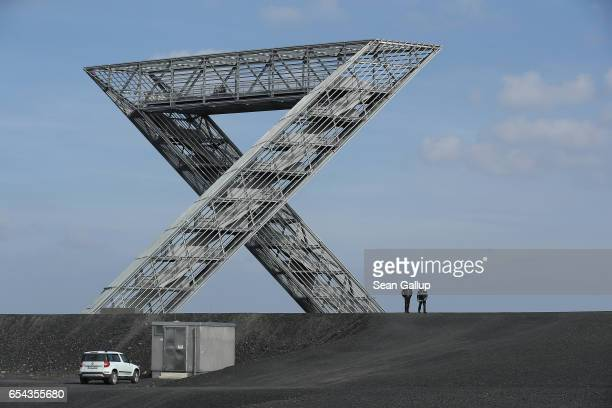 Two men walk under the Saarpolygon on a hill that is actually a slag heap from a former nearby coal mine on March 15 2017 in Ensdorf Germany The hill...