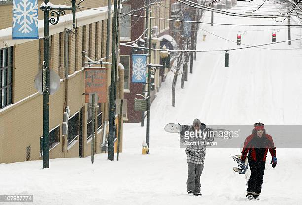 Two men walk with their snowboards after a snowfall of over sixinches hit this area of the Blue Ridge Mountains on January 10 2011 in downtown...