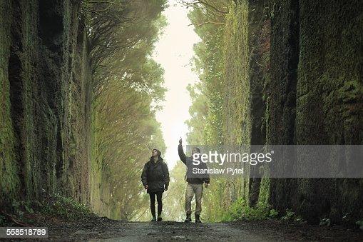 Two men walking between massive rocky walls