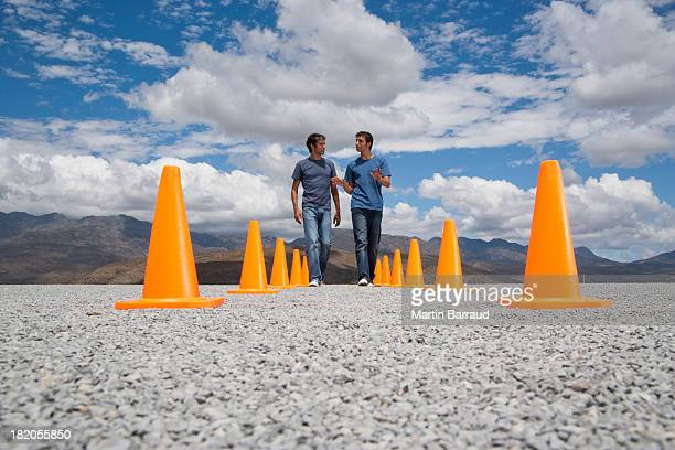 Two men walking by each other flanked by two rows of safety cones