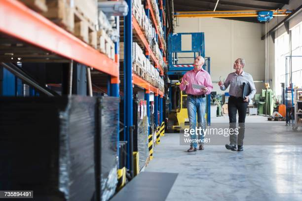 Two men walking in industrial hall looking at shelves
