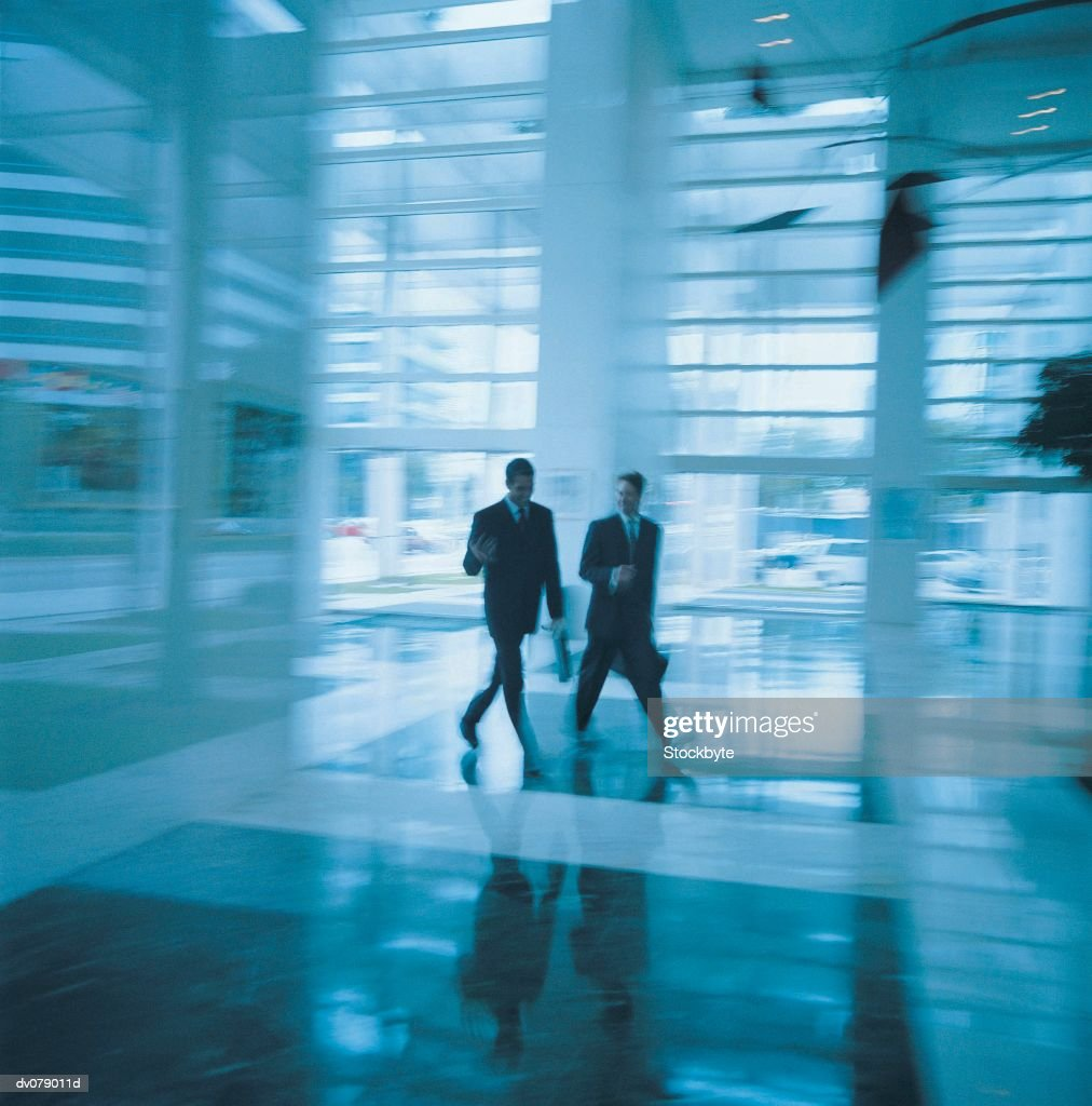 Two men walking through foyer of building : Stock Photo