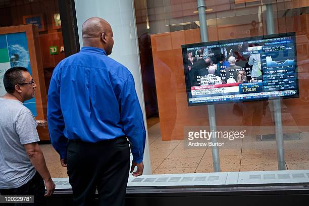 Two men watch a breaking news alert as the House of Representatives successfully pass a bill to raise the national debt limit on a television...
