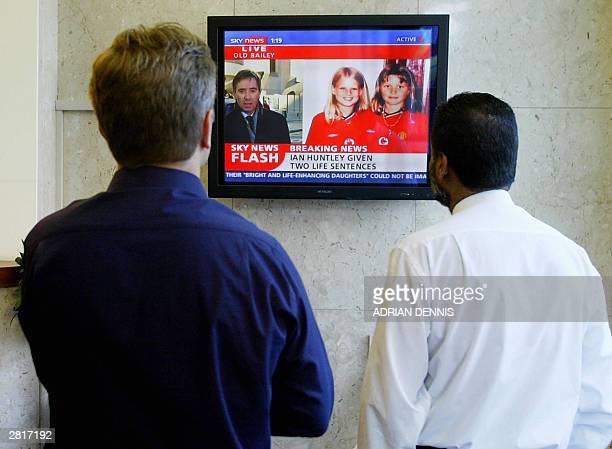 Two men watch a TV monitor as Ian Huntley is sentenced to two life terms in prison for murdering 10yearold school girls Holly Well and Jessica...