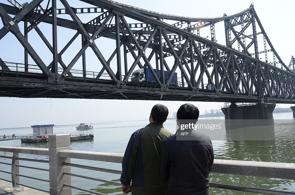 Two men watch as a truck crosses the Sino-Korean Friendship Bridge towards the Chinese border city of Dandong, northeastern Liaoning province, from the North Korean border town of Siniuju on April 10, 2013. The biggest border crossing between North Korea and China has been closed to tourist groups, a Chinese official said on April 10 as nuclear tensions mounted, but business travel was still allowed.