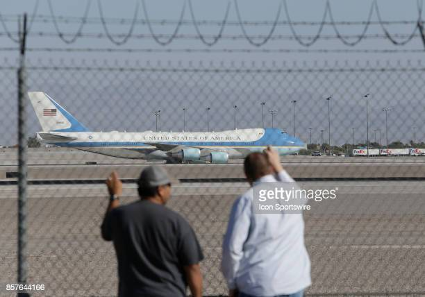 Two men watch as Air Force One with US President Donald Trump and First Lady Melania Trump taxi down to parking at McCarran International Airport in...