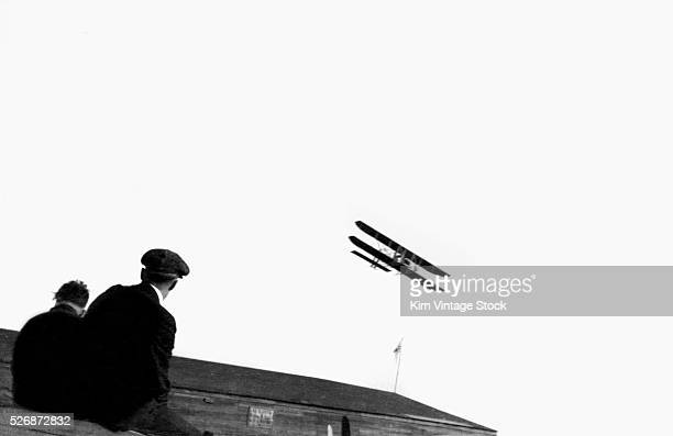 Two men watch as an early biplane flies over a field in Ohio
