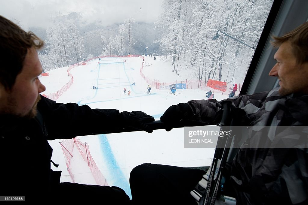 Two men watch competitors take part in the Ski Cross championships from a gondola above the course in Rosa Khutor, one of the 2014 Winter Olympics venues, in the Black Sea city of Sochi on February 19, 2013. With a year to go until the Sochi 2014 Winter Games, construction work continues as tests events and World Championship competitions are underway. AFP PHOTO / LEON NEAL
