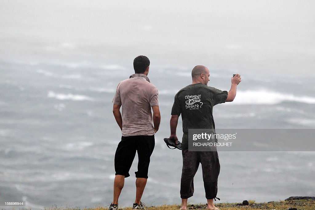 Two men watch high waves hitting the coastline on January 3, 2013 in Le Port, western part of French overseas' island of La Reunion, as cyclone Dumile approaches and authorities declare today a red alert that forbid people to leave their homes.