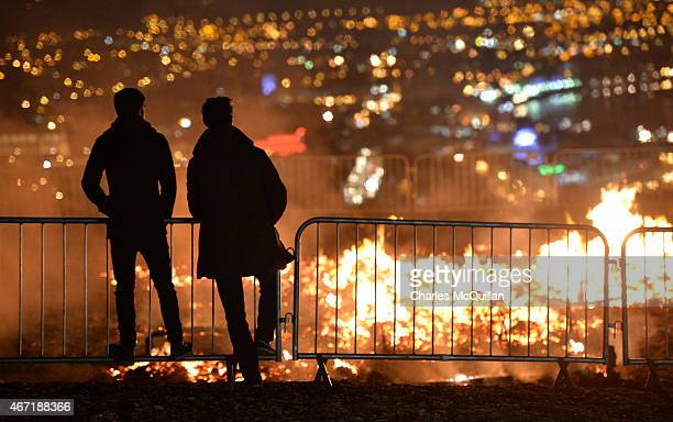 Two men watch the dying embers of the Temple by renowned Burning Man artist David Best after it was set ablaze on March 21 2015 in Londonderry...