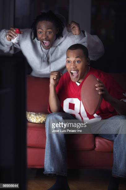 Two men watching television and cheering for team with snacks