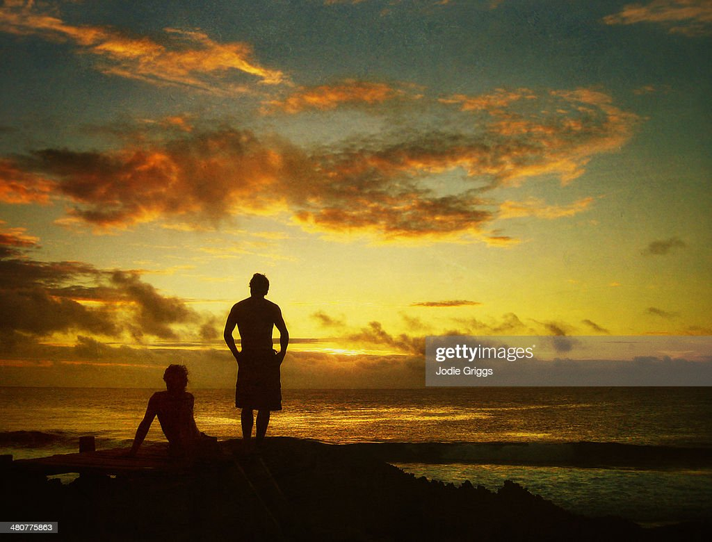 Two men watching the sun set over the ocean