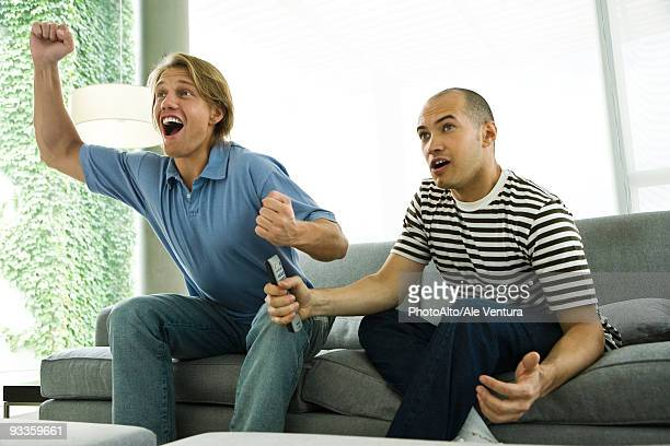 Two men watching TV and cheering on sofa