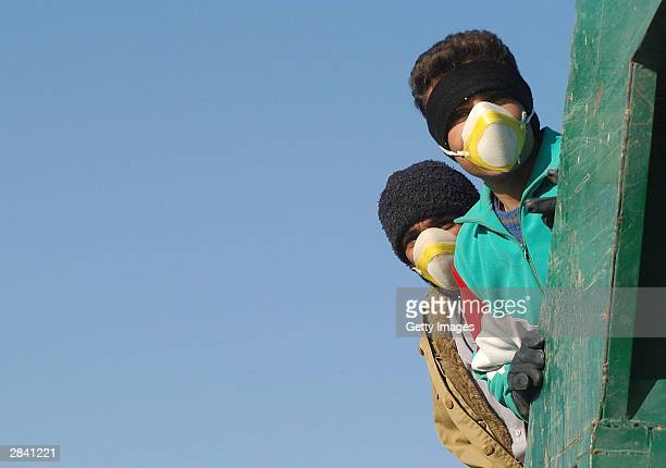 Two men wear protective masks January 2 2003 in Bam Iran A week after a massive earthquake shattered Bam killing some 30000 people residents are...