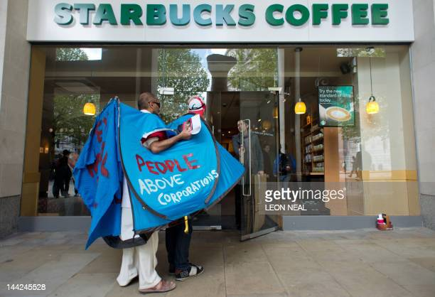 Two men wearing a tent attempt to enter a branch of Starbucks coffee shop near Saint Paul's cathedral in central London during an 'Occupy'...