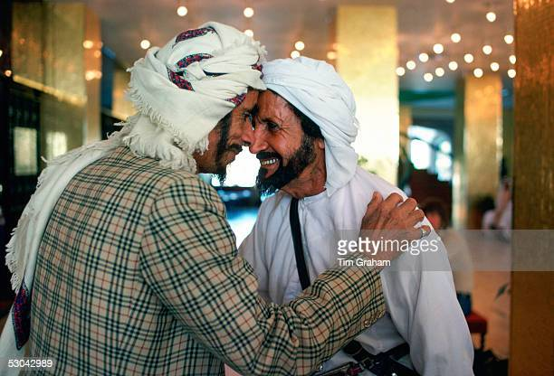 Two men wearing arab headdresses giving the traditional arab greeting in the Hilton Hotel at Al Ain Abu Dhabi United Arab Emirates