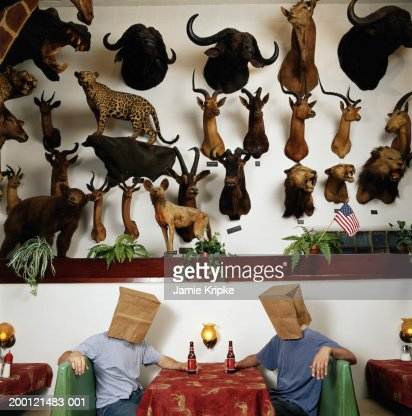 Two men wearing brown bags on heads at table under dead animals : Stock Photo