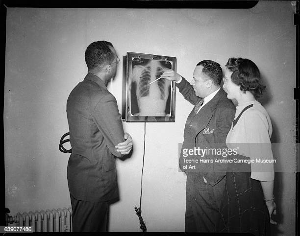 Two men wearing dark suits and woman wearing light colored top and dark grid patterned skirt observing xray of lungs circa 19401946