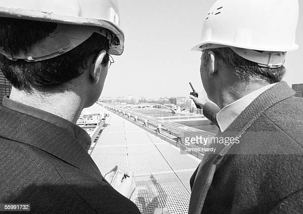 Two men wearing hard harts, talking, rear view, b&w