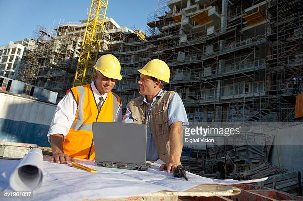 Two Men Wearing Hard Hats Looking at a Laptop Computer on a Building Site