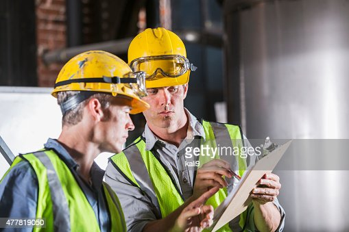 Two men wearing hardhats, vests and safety glasses