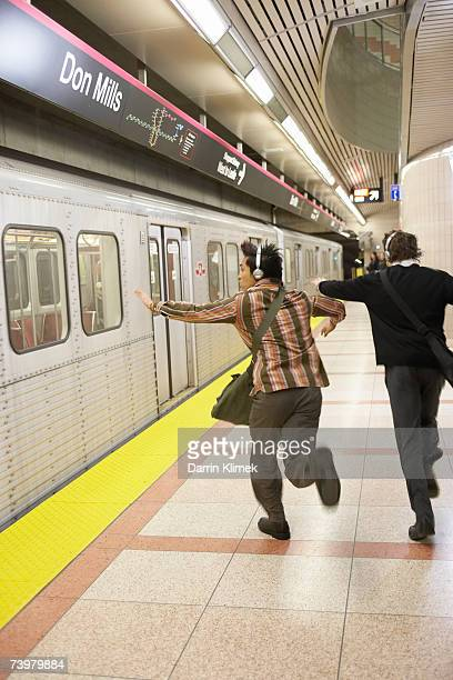 Two men wearing headphones running to catch subway train, rear view