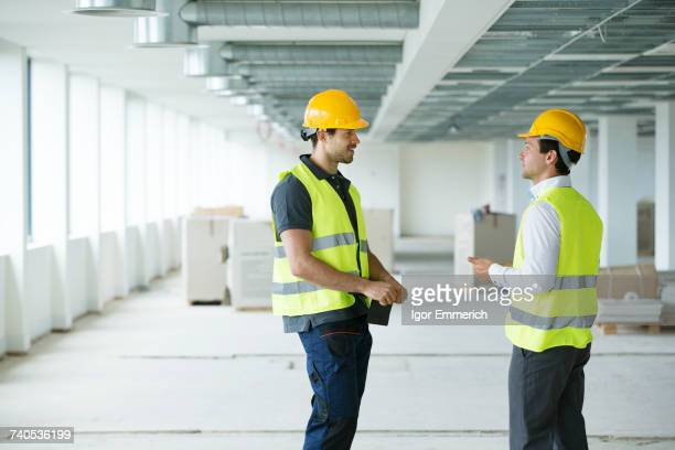 Two men wearing hi vis vest, having discussion in newly constructed office space