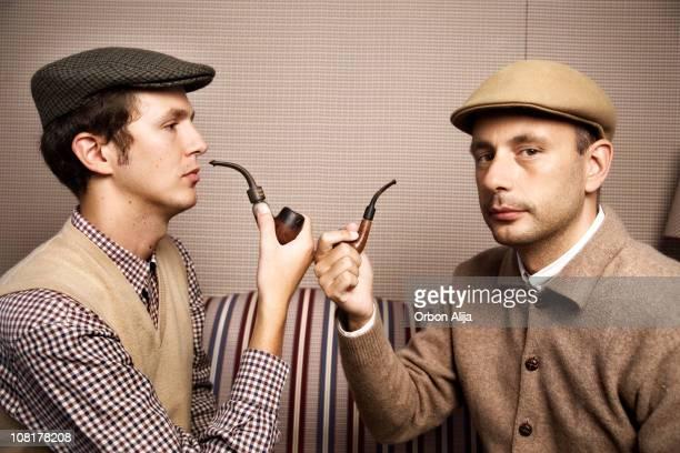 Due uomini indossano cappelli e tubi Newsboy fumatori