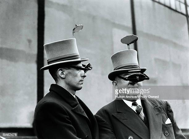 Two men wearing 'periscope' top hats (B&W)
